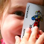 child holding a joker card in front of her face_b