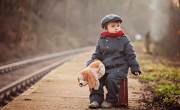 c_young boy say on suitcase next to railway track