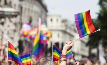 A spectator waves a gay rainbow flag at an LGBT gay pride march in London