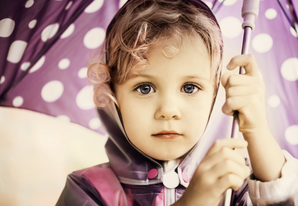 child holding a purple dotted umbrella