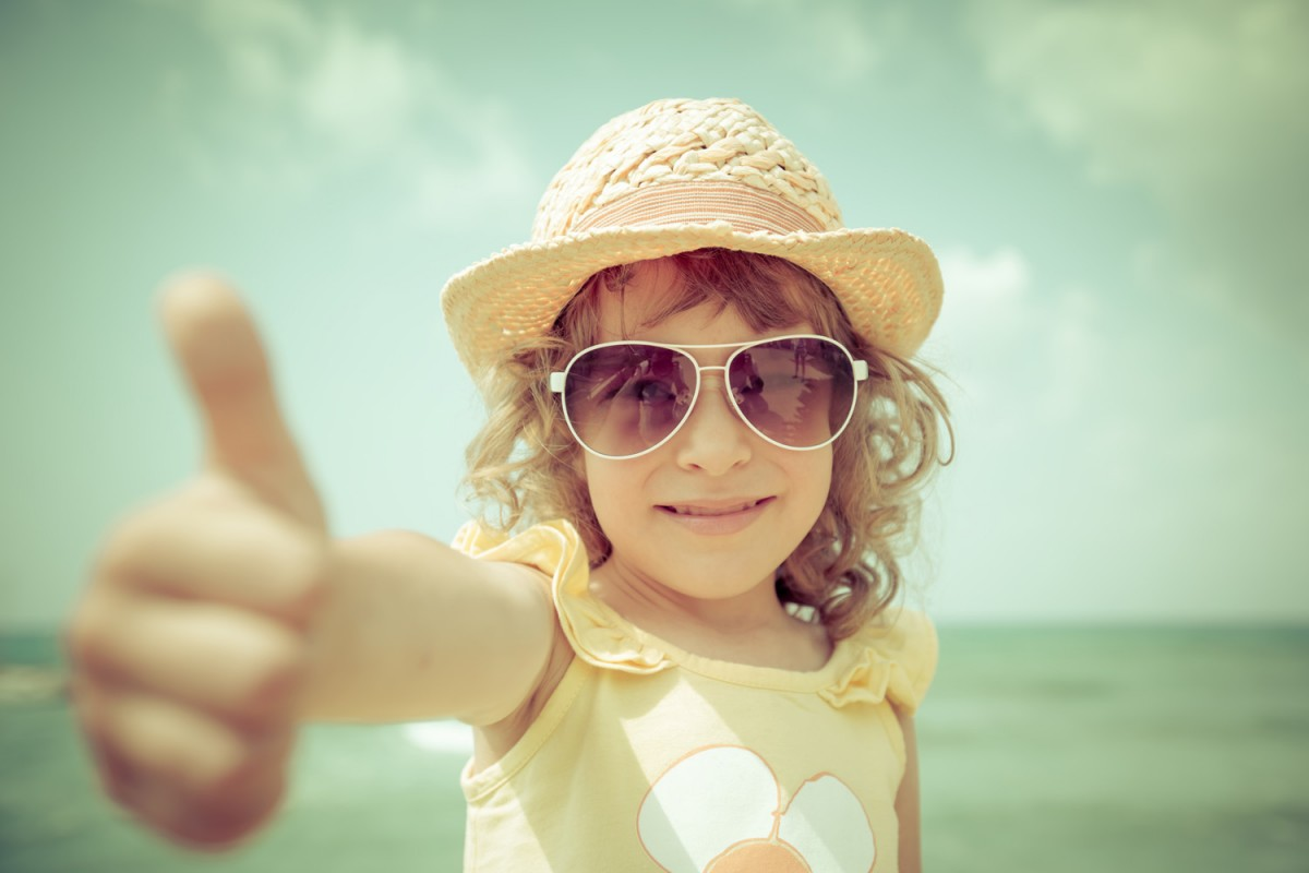 girl in sunglasses giving thumbs up