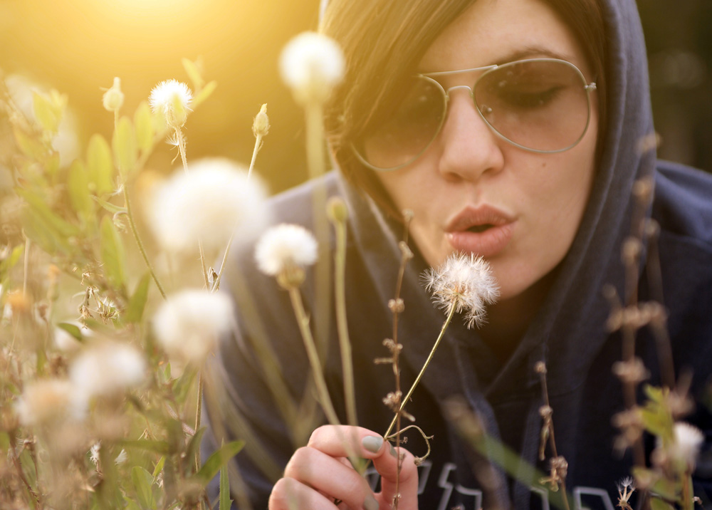 woman blowing on dandelions